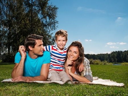 Young family with their child lying on a blanket outdoors  photo