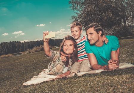 mujer hijos: Familia joven con su hijo haciendo selfie sobre una manta al aire libre