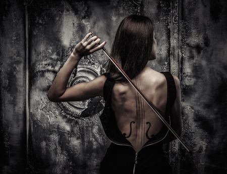 Woman in dress with violin body art holding bow photo