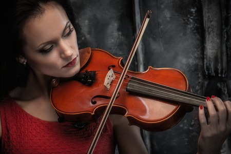 fiddle: Young woman in red dress playing violin in mystic interior