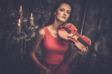 gothic woman: Young woman in red dress playing violin in mystic interior