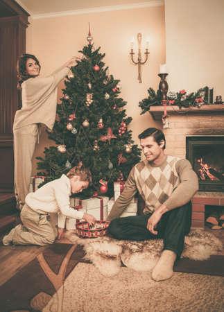 Happy family decorating Christmas tree  photo