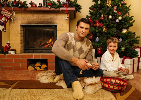 Young father with his son near fireplace in Christmas decorated house interior  photo