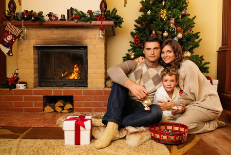Family near fireplace in Christmas decorated house  photo