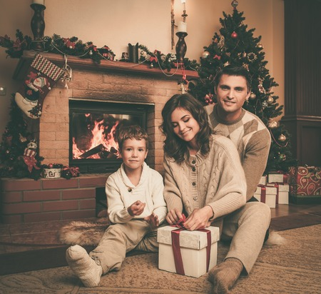 men socks: Family near fireplace in Christmas decorated house interior with gift box