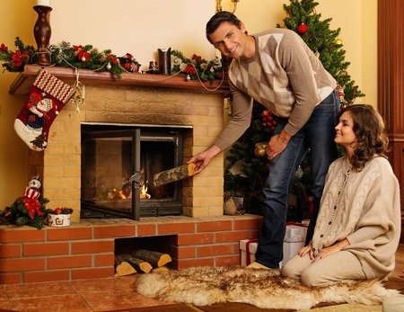 Couple putting log into  fireplace in Christmas decorated house interior  photo