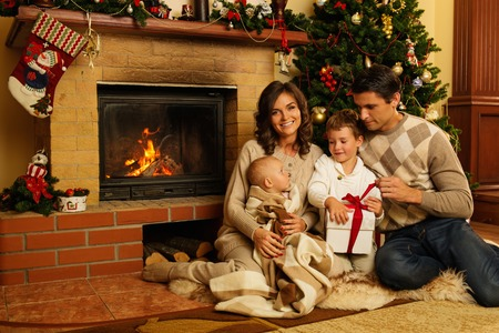 Family near fireplace in Christmas decorated house interior with gift box photo