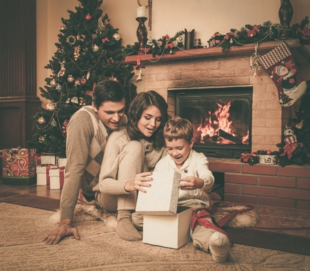smile christmas decorations: Family near fireplace in Christmas decorated house interior with gift box