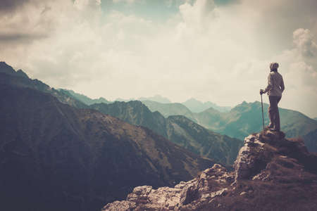 trekking pole: Woman hiker on a top of a mountain  Stock Photo