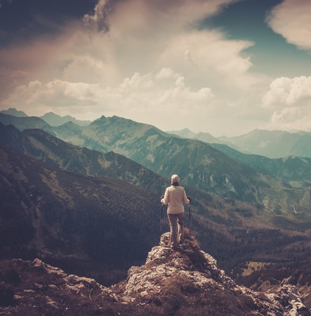 hiking stick: Woman hiker on a top of a mountain  Stock Photo