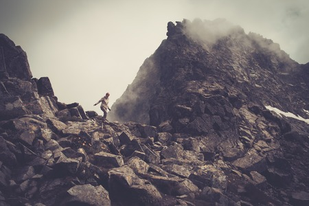 cliff edge: Woman hiker walking in a mountains  Stock Photo
