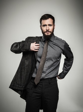 put: Handsome man with beard putting on jacket