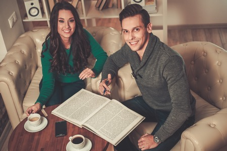 cowering: Young man and woman with book and coffee behind table Stock Photo