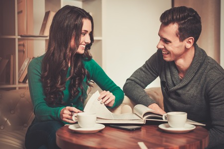 cowering: Couple with coffee and book discussing something in cafe Stock Photo