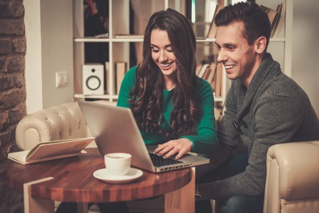 Young couple with laptop and coffee behind table photo