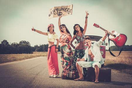 simbolo de la paz: Autoestopistas hippie multi-étnicas con la guitarra y el equipaje en el buen camino