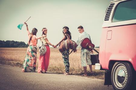 persona feliz: Amigos hippies multiétnicos con la guitarra y el equipaje
