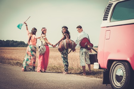 happy person: Multi-ethnic hippie friends with guitar and luggage