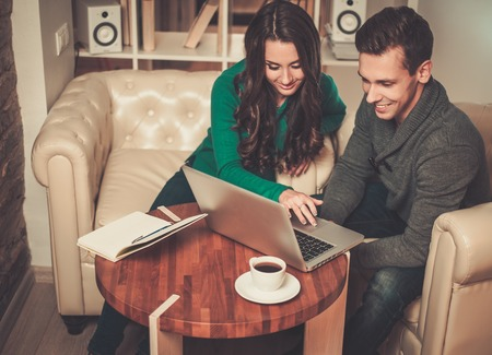 cowering: Young couple with laptop and coffee behind table