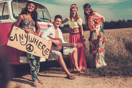 Multi-ethnic hippie hitchhikers with guitar and luggage on a road photo
