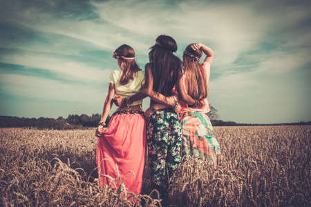 mujer hippie: Niñas hippie multi-étnicas en un campo de trigo
