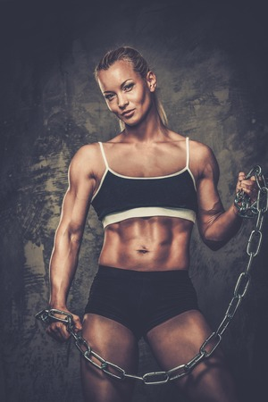 Beautiful muscular bodybuilder woman holding chains photo