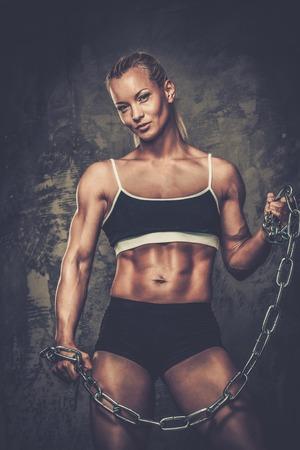 body pump: Beautiful muscular bodybuilder woman holding chains
