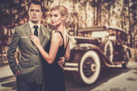 Beautiful retro couple against vintage car photo