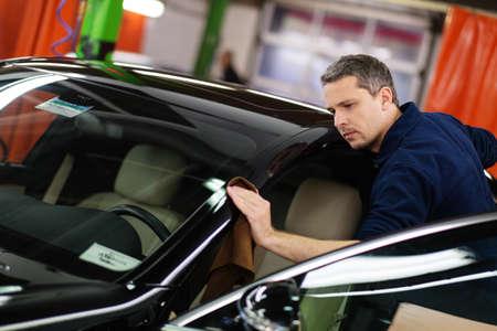 garage automobile: Man travailleur polissage voiture sur un lavage de voiture