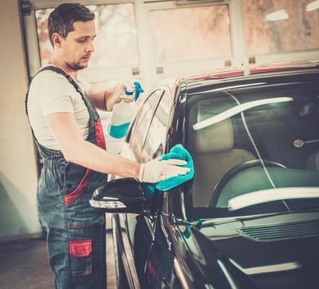 lavar: Trabajador en un auto lavado del coche con un spray