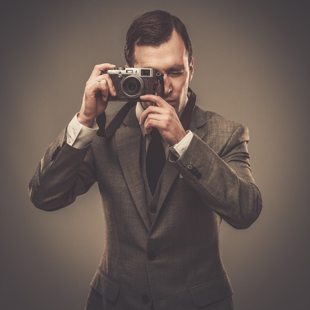 Well-dressed man with a retro camera photo