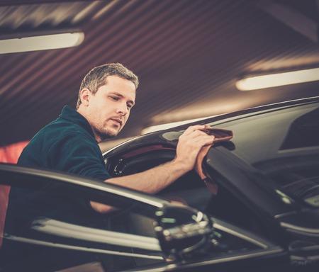 garage automobile: Homme travailleur polissage voiture sur un lavage de voiture