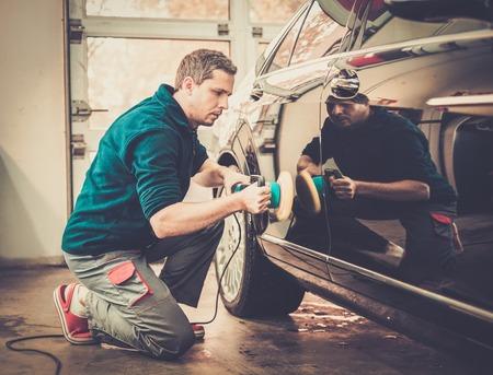 garage automobile: L'homme sur une station de lavage de voiture de polissage avec une machine à ongles