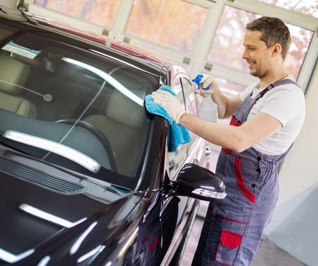 car polish: Worker on a car wash cleaning car with a spray
