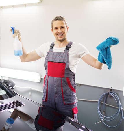 lavar: Trabajador feliz en un túnel de lavado con un spray
