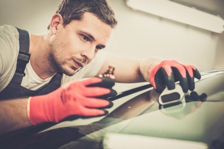 coating: Worker on a car wash applying anti rain coating on a windshield Stock Photo