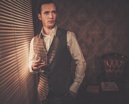 Man with a glass near a window photo