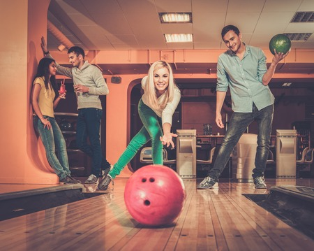 Blond smiling girl throwing ball in a bowling club photo