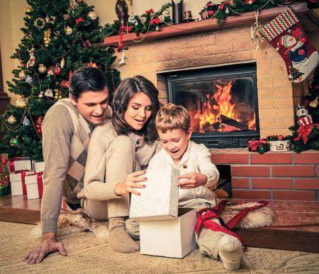 camino natale: Famiglia vicino al camino a Natale decorato casa interiore con confezione regalo Archivio Fotografico