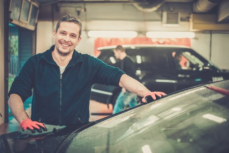 car wash: Cheerful worker wiping car on a car wash