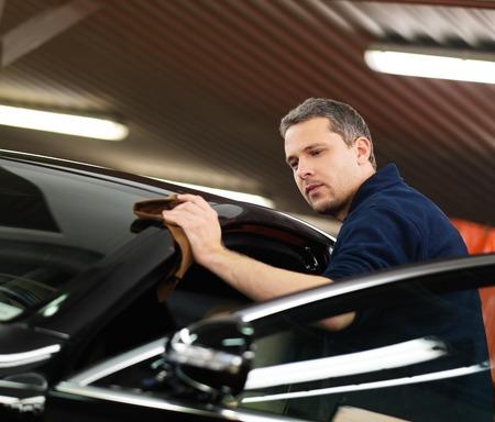 lavar: Hombre trabajador de pulido del coche en un túnel de lavado
