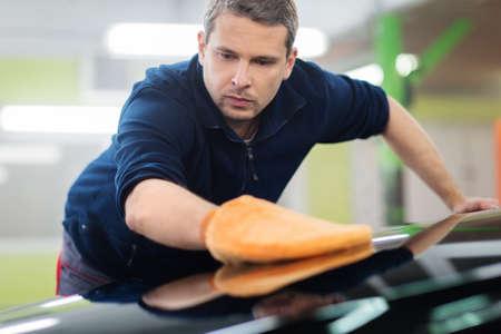 body paint: El trabajador del hombre pulir coche en un t�nel de lavado