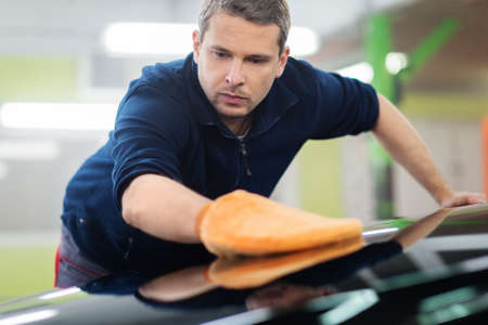 body check: Man worker polishing car on a car wash