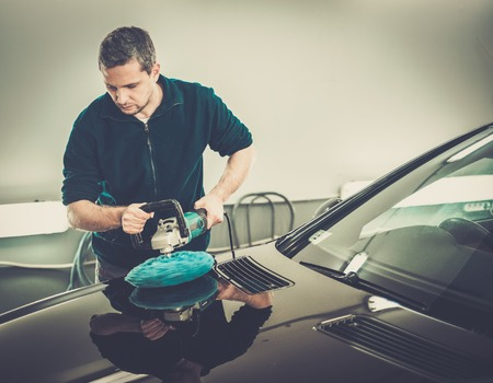 Man on a car wash polishing car with a polish machine photo