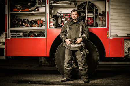 Cheerful firefighter near truck with equipment Stock Photo