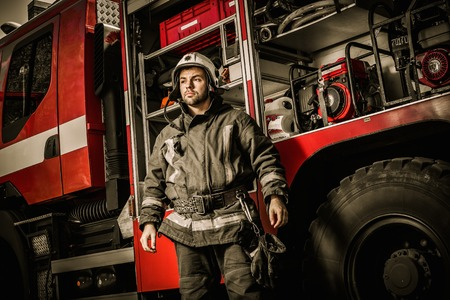 Cheerful firefighter near truck with equipment photo