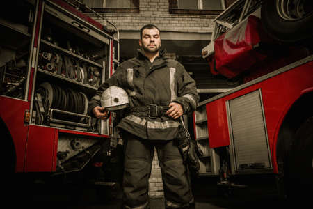 fire department: Cheerful firefighter near truck with equipment Stock Photo