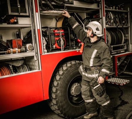 fire shield: Fireman taking equipment from firefighting truck