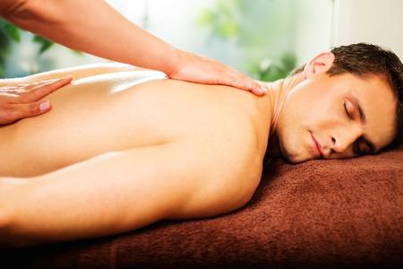 Handsome man having massage in spa salon Stock Photo