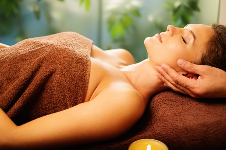 massage table: Young woman having face massage in a spa salon Stock Photo